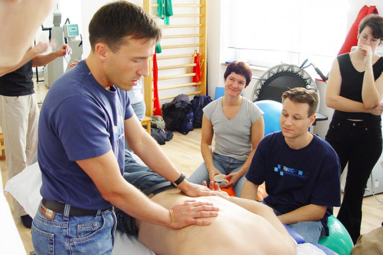 Mann führt Massage vor Gruppe durch