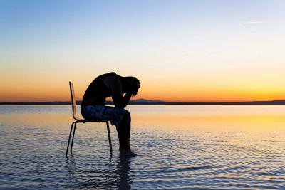 Mann sitzt im Sonnenuntergang