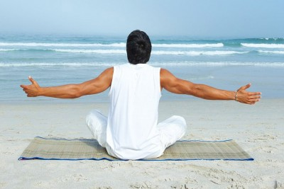 Mann sitzt am Strand und genießt Meeresluft