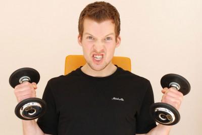 Mann mit Hanteln und anstrengendem Gesichtsausdruck
